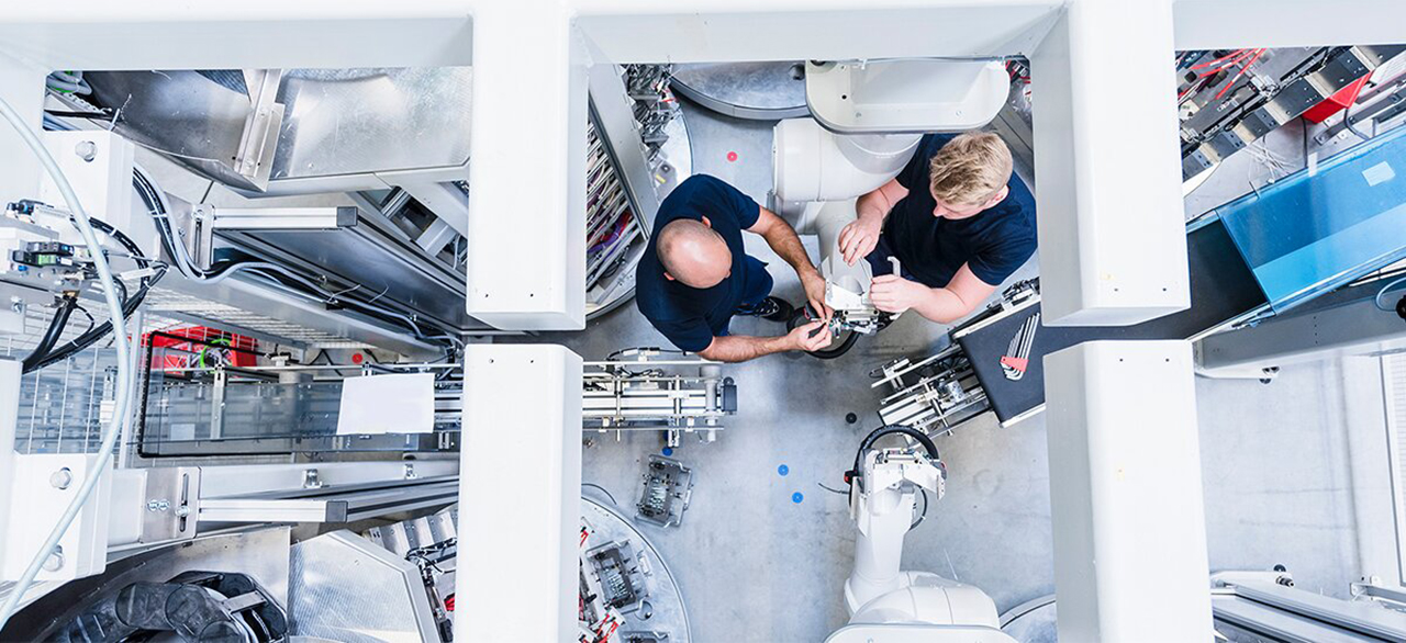 Top view of two colleagues working at industrial robot