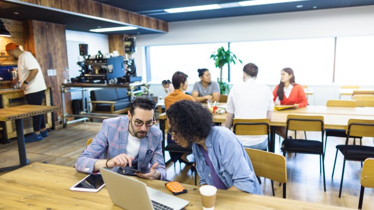 Multi-ethnic people are working together in a modern co-working space.