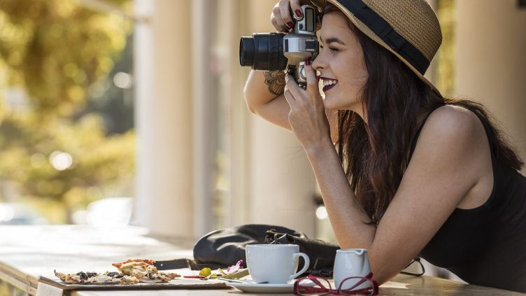young beautiful traveler happily taking photos with camera at cafe