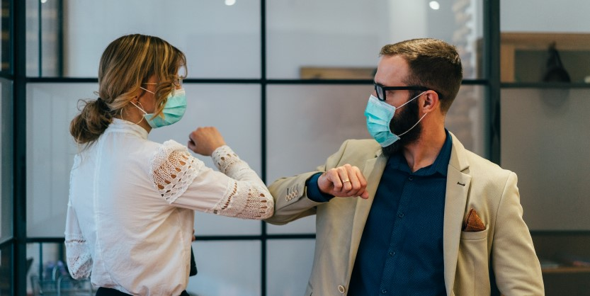 A man and a women greeting each others while wearing masks